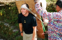 A trekker tries the weight of a porters load